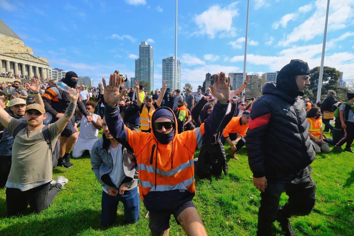Mielenosoittajat ovat polvistuneet nurmikolle kädet ylhäällä pystyssä.