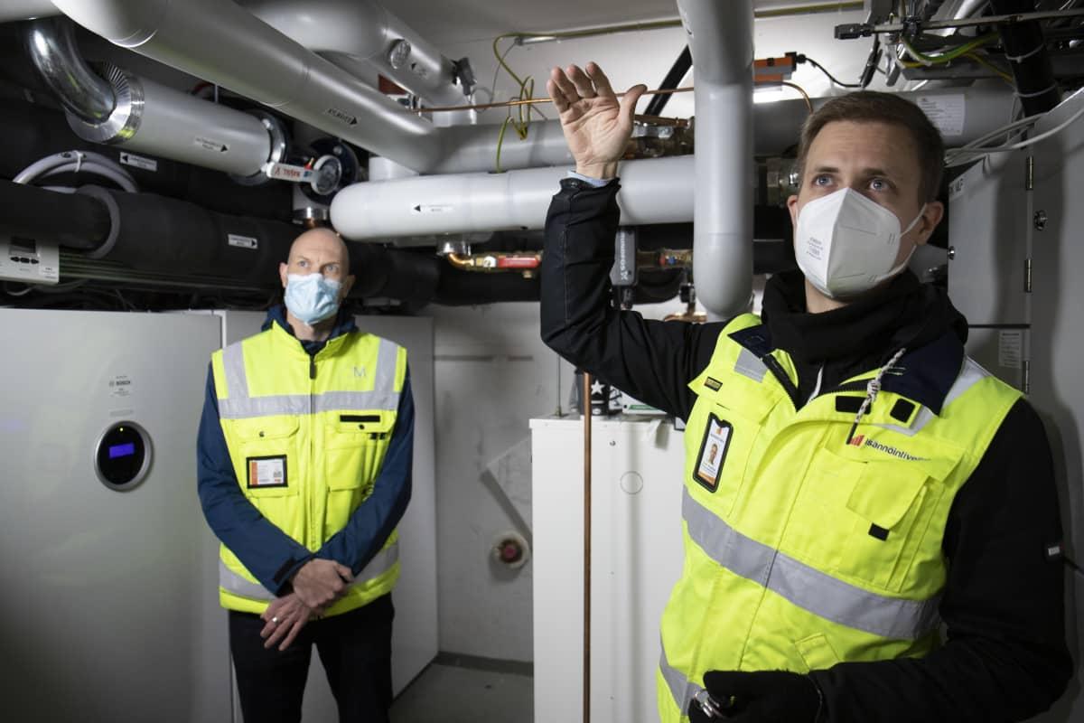Energiainsinööri Matti Keinänen ja isännöitsijä Jaani Wahlman lämmönjakohuoneessa.