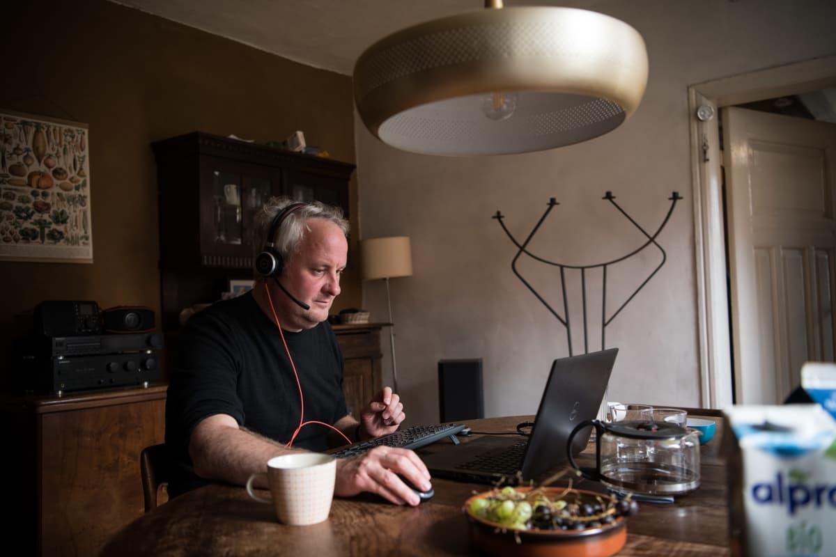 Mies tekee tietokoneella töitä pöydän ääressä.