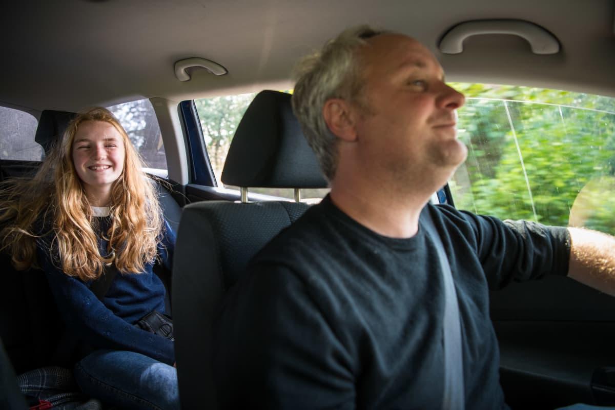 Mies ajaa autoa ja takapenkillä hymyilee nuori nainen.