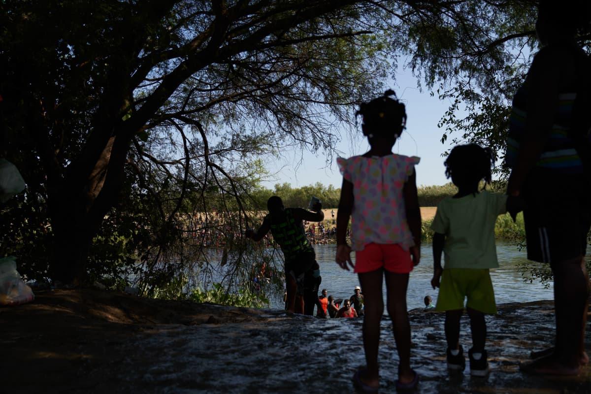 Kaksi pientä lasta katselee rannalla paikkaa, jossa siirtolaiseksi joutuneet ihmiset ylittävät suuren joen.