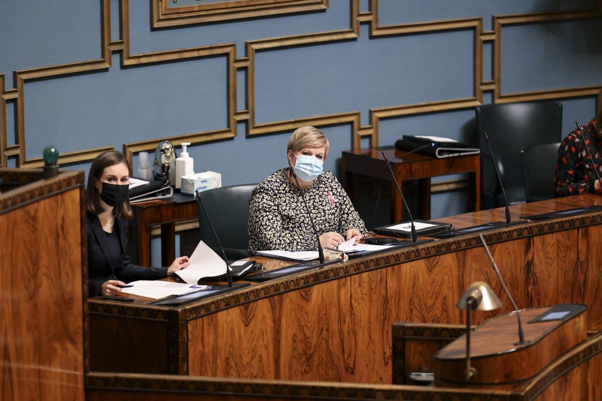 Annika Saarikko puhuu eduskunnassa, vieressä pääministeri Marin.