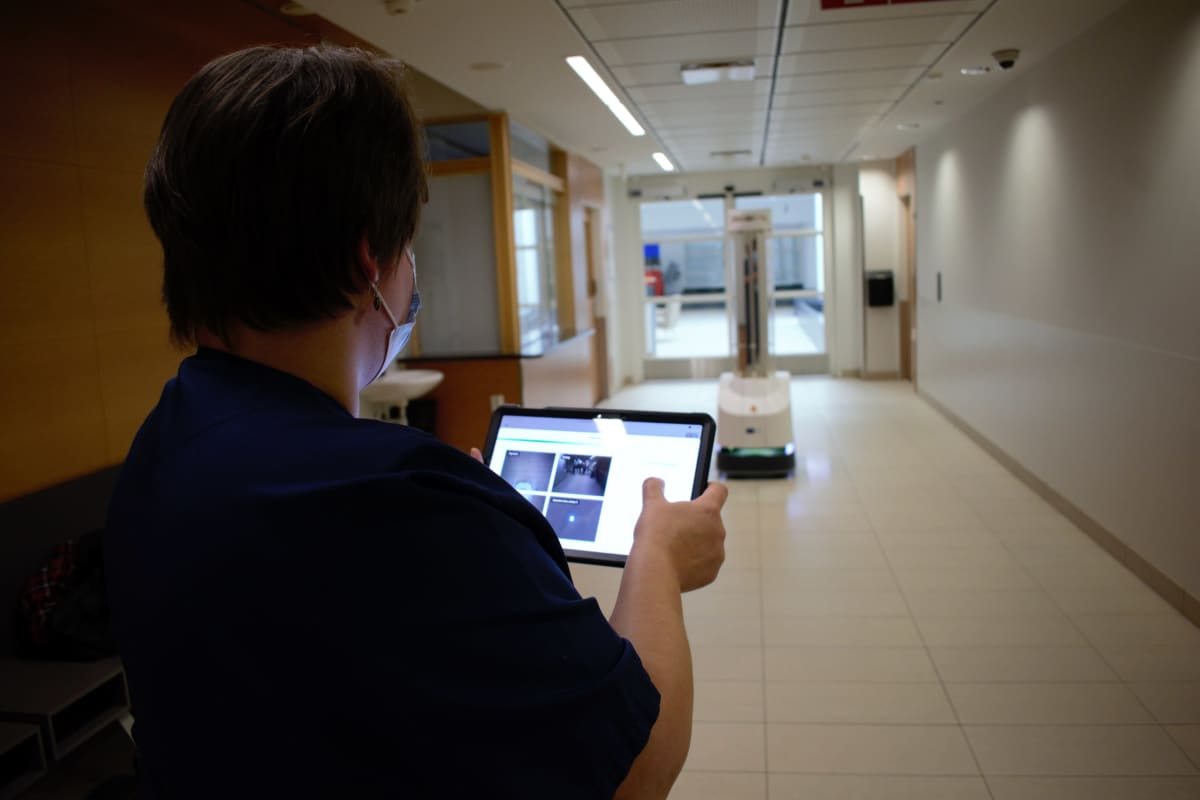 Työnjohtaja Hannele Mattila harjoittelee desinfiointirobotin käyttöä Tyksin teho-osastolla.
