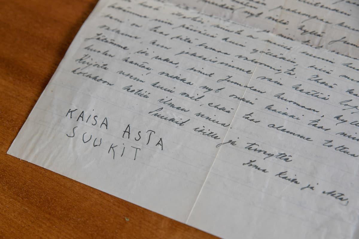 Tikkukirjaimilla kirjoitetut lasten Kaisan ja Astan nimet sodanaikaisen kirjeen lopussa