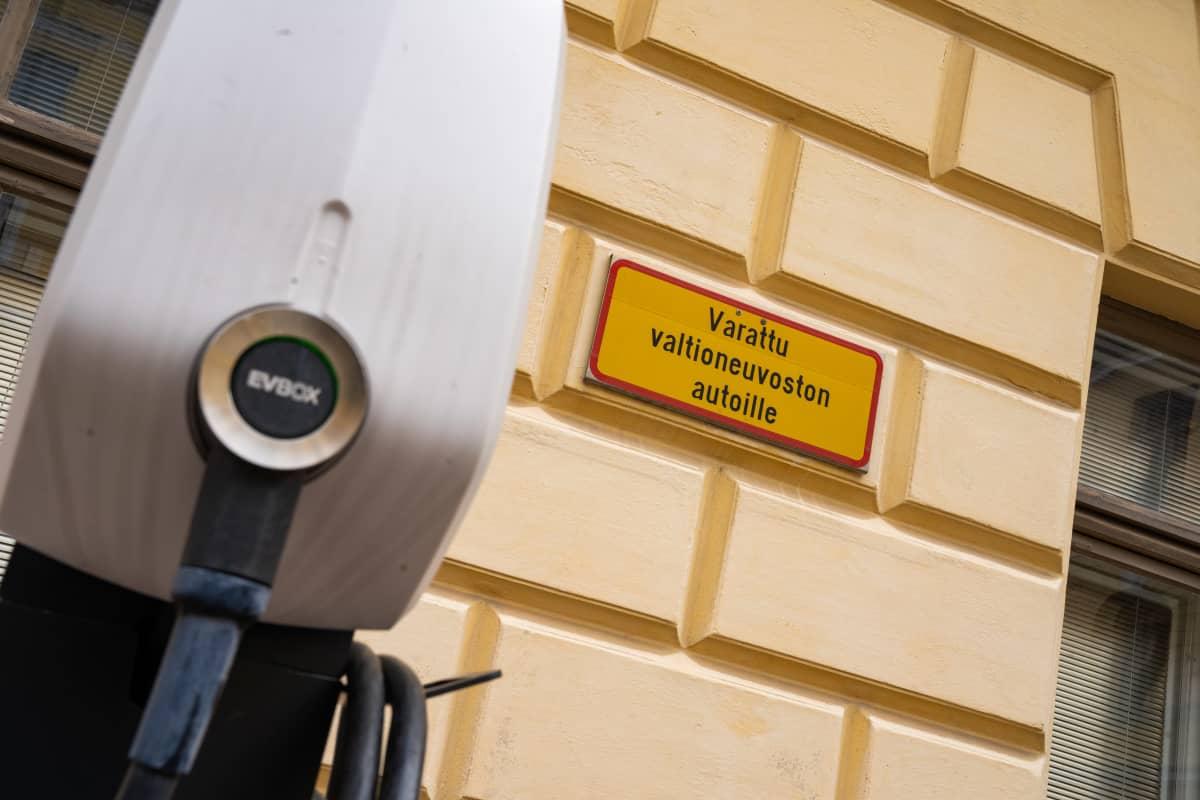 yleiskuva - hybridikäyttöisen virka-auton lataustolppa ja takana olevassa seinässä kyltti, jossa lukee: varattu valtioneuvoston autoille