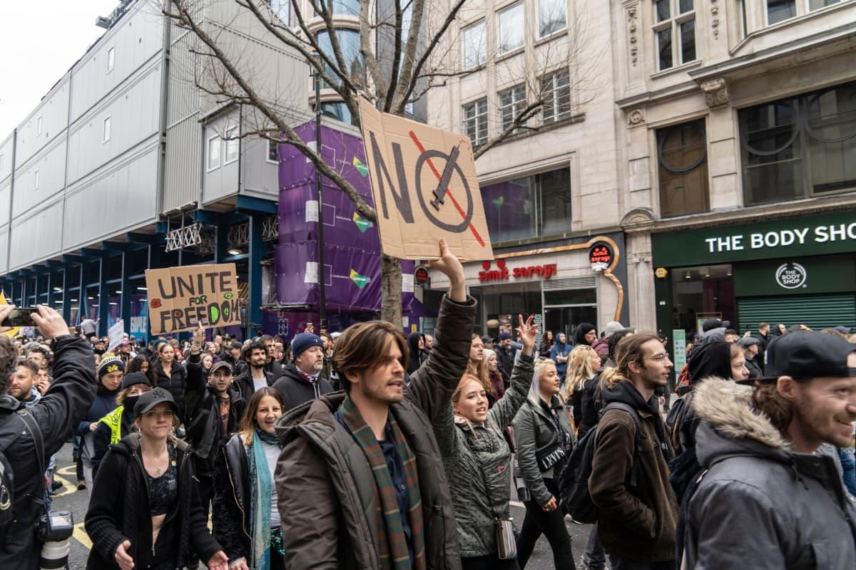 Mies pitelee rokotevastaista kylttiä Lontoossa sulkutoimenpiteitä vastustavassa mielenosoituksessa maaliskuussa.