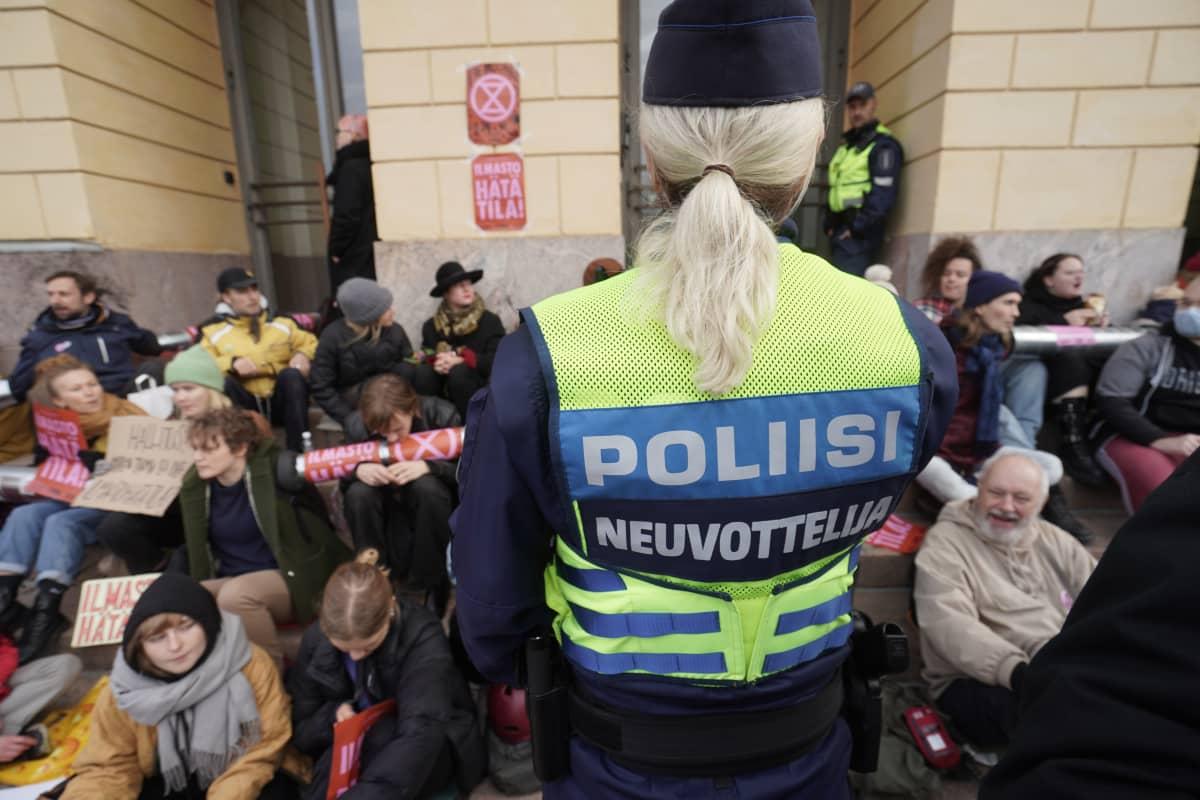 Poliisi neuvottelee mielenosoittajien kanssa poistumisesta.