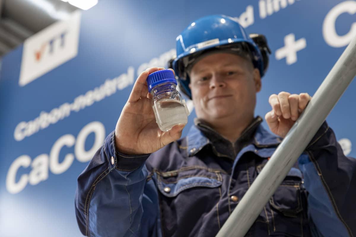 VTT:n johtava tutkija Eemeli Tsupari esittelee polttoainepulloa, jonka valmistamiseen on käytetty rumpu-uunissa eroteltua hiilidioksidia.