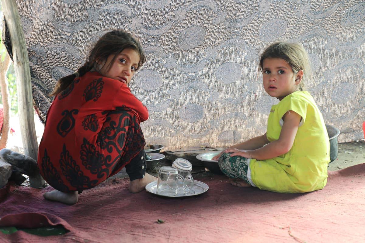 Pakolaistytöt pesivät astioita leirillä Kabulissa.