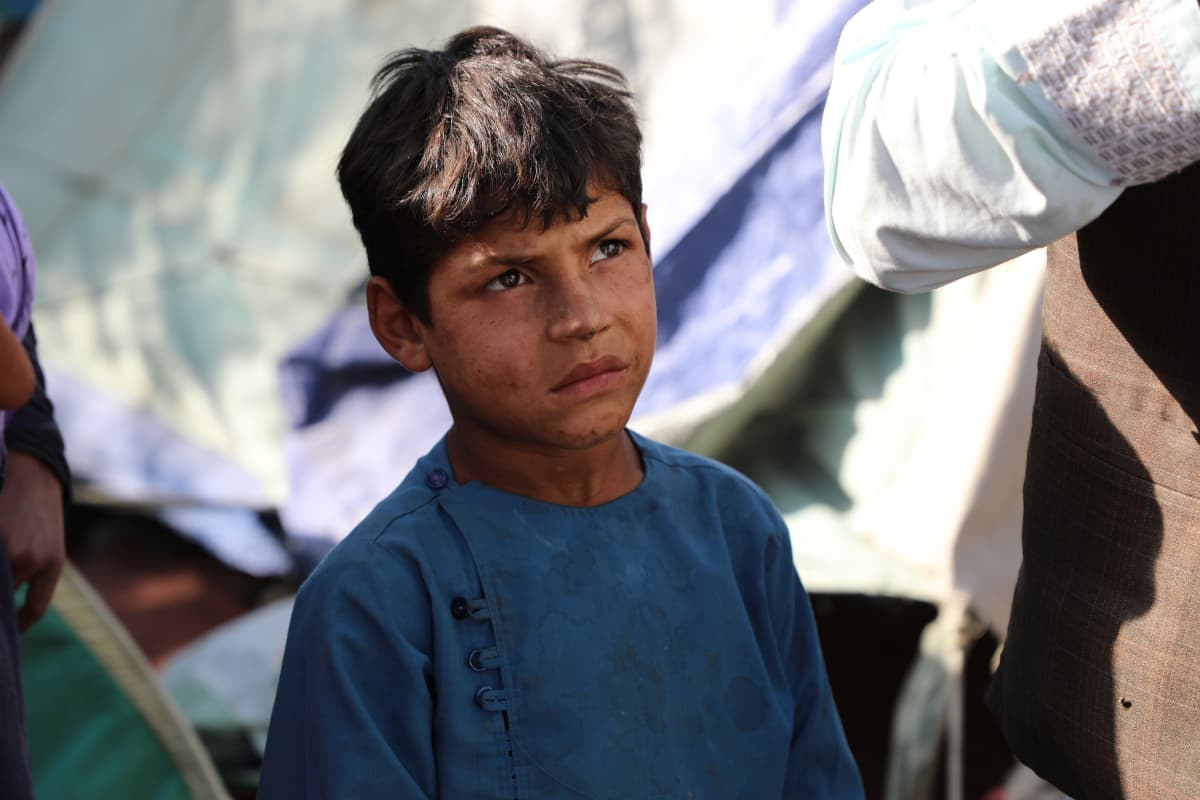 Poika katselee aikuisia pakolaisleirillä Kabulissa.
