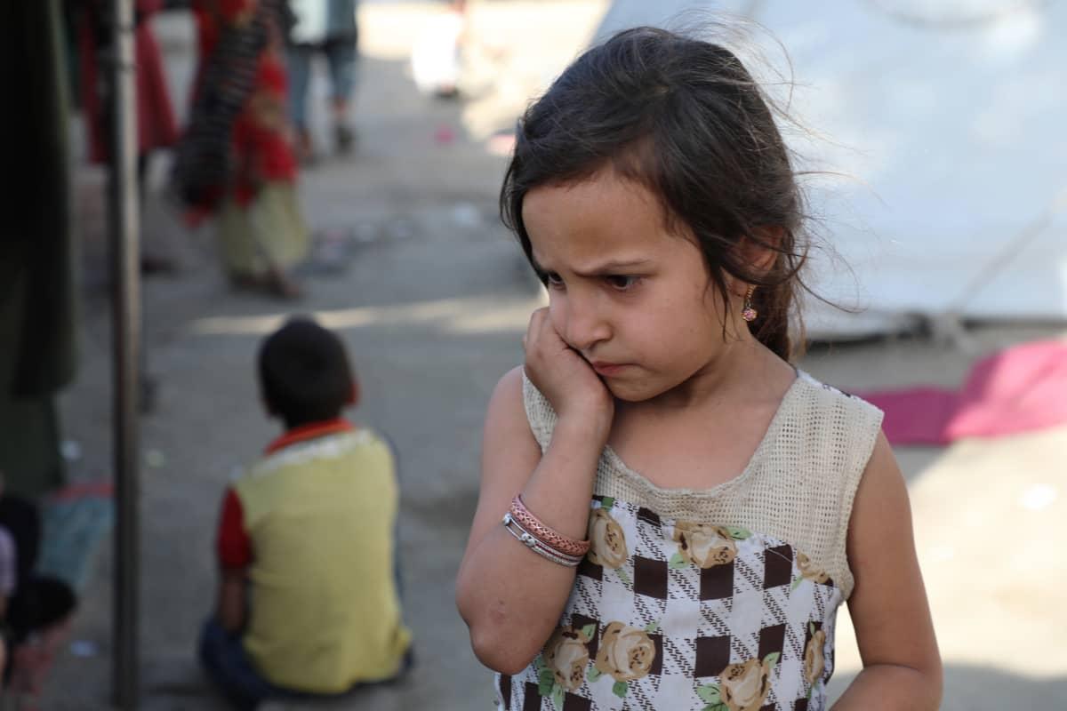 Tyttö nojaa kädellään poskeen kabulilaisella pakolaisleirillä