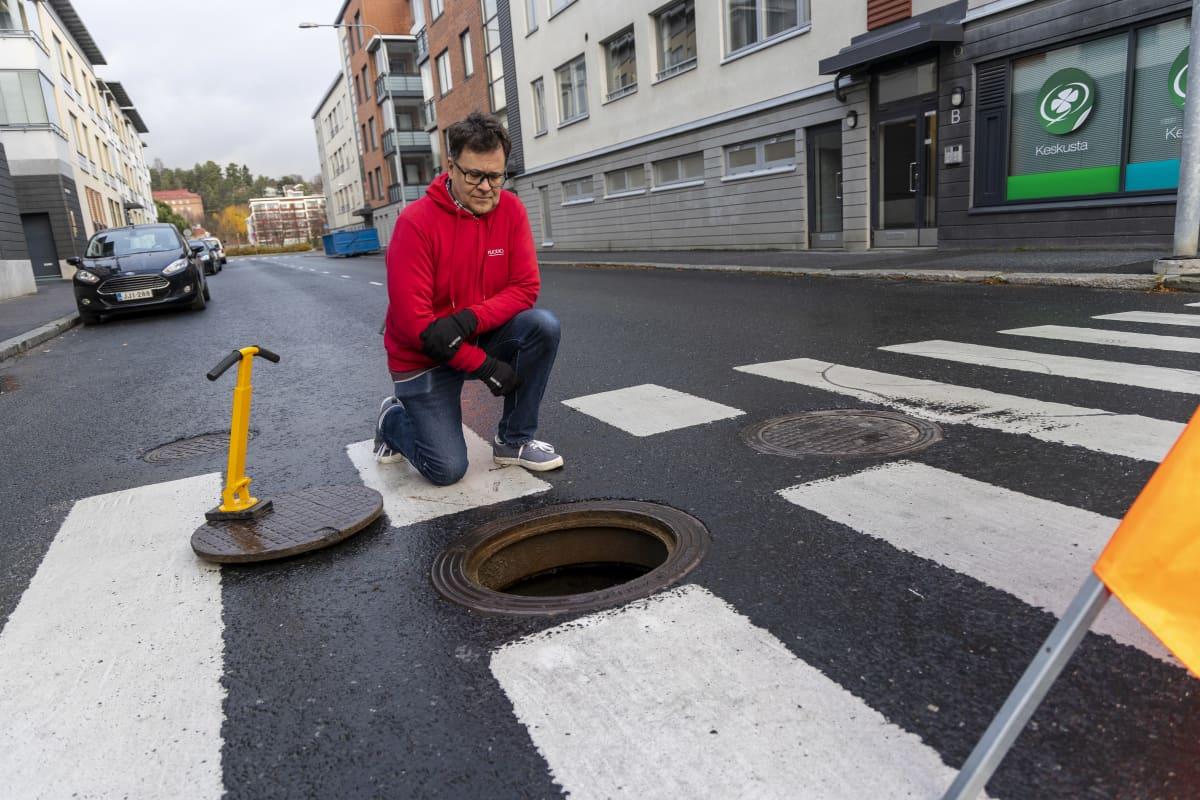 ISMO HEIKKINEN kaupungininsinööri, Kuopion kaupungilta tarkastelee viemärin aukiolevaa kantta
