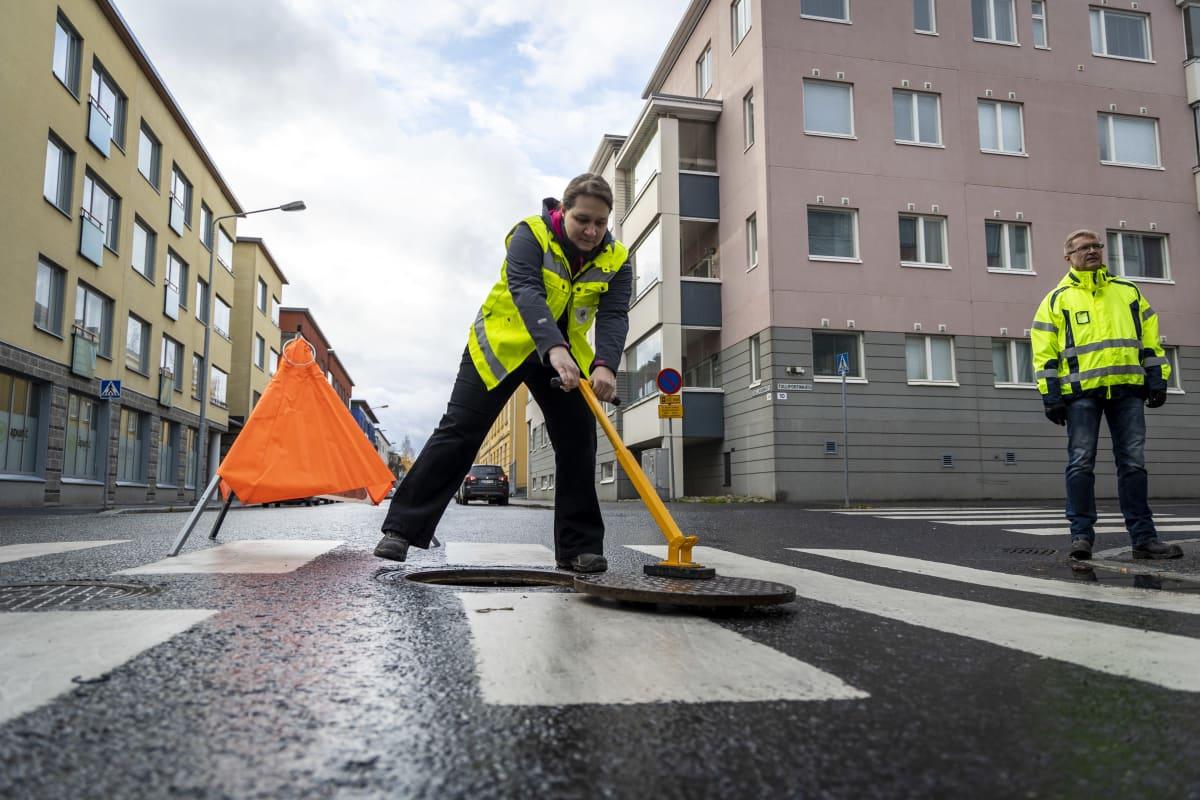 Katja Ylönen, valvoja, Kuopion kaupungilta avaa kaivonkantta Kuopion keskustassa. Vieressä seisoo Jarmo Laaksoviitta.