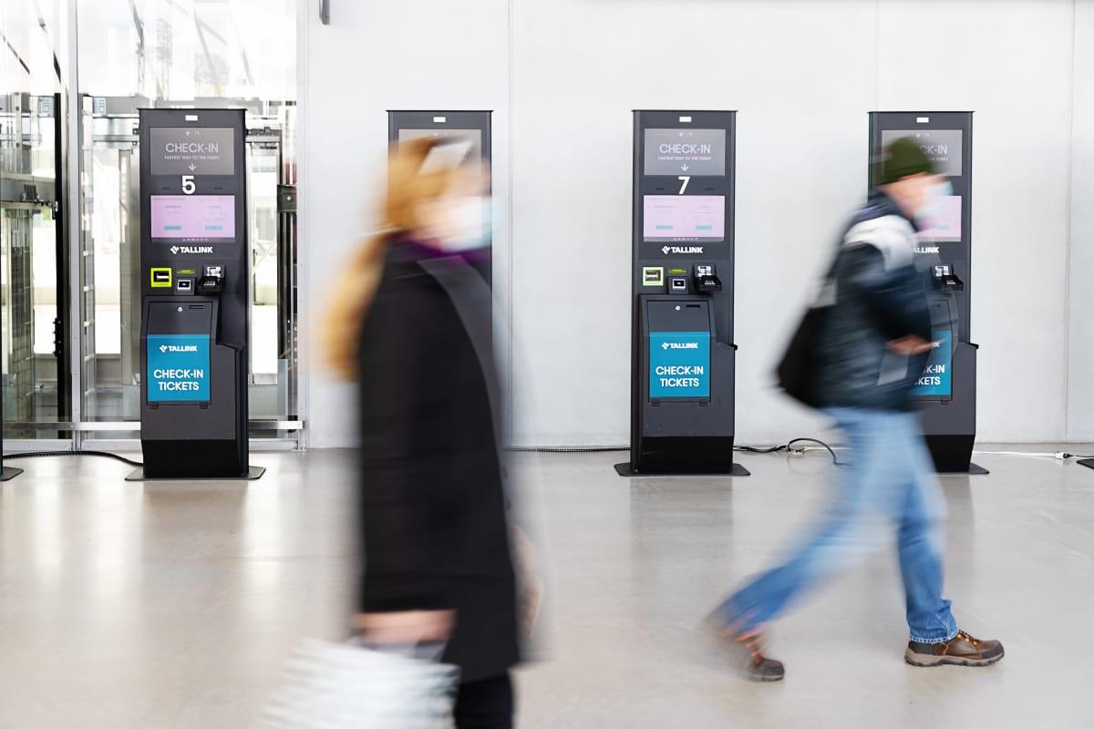 Lippuautomatteja Länsiterminaali 2:ssa, ohikulkevia ihmisä, ei tunnistettavia.