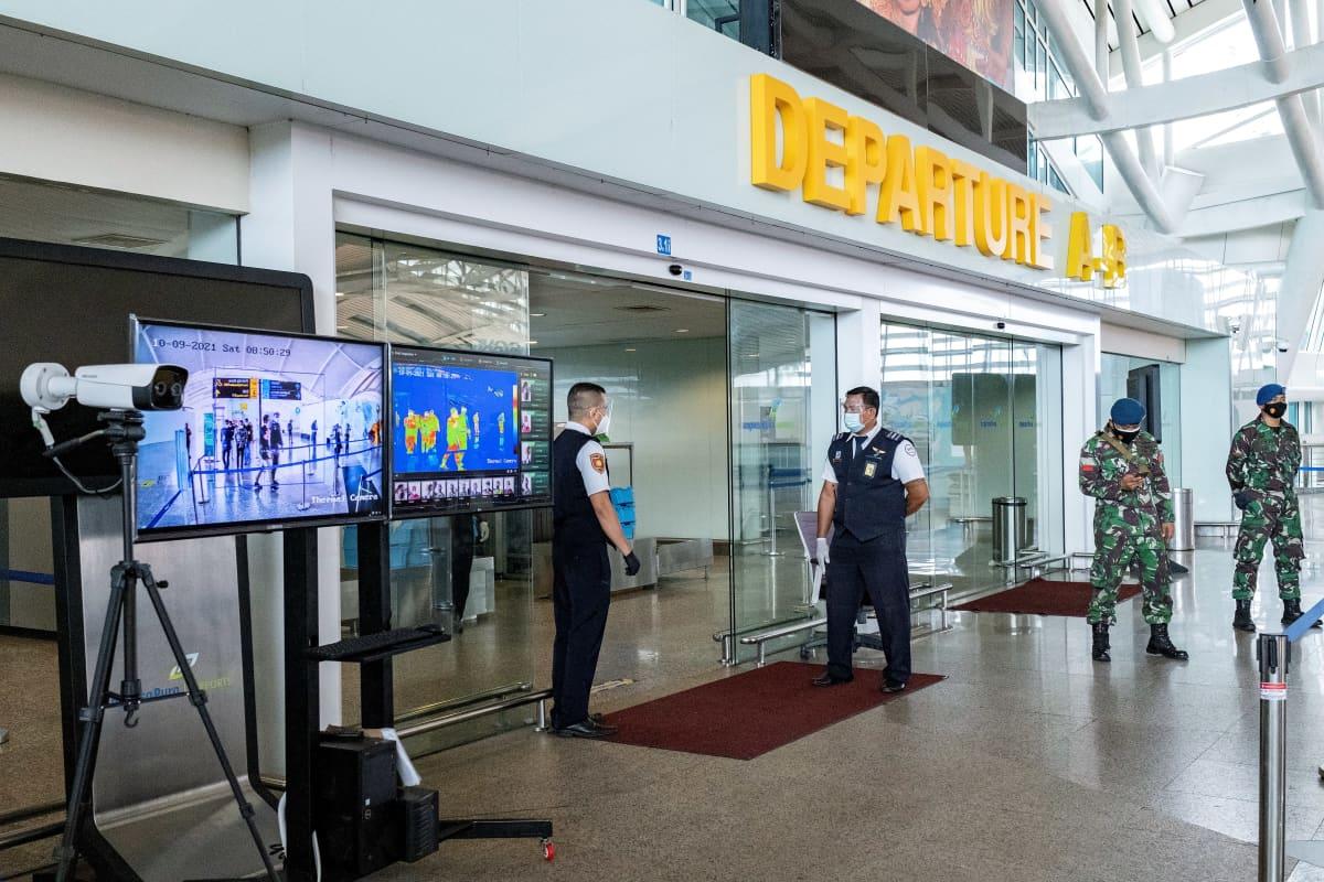 Kaksi työntekijää seisoo maskeissa ovien luona. Heidän lähellään seisoo kaksi sotilasta.