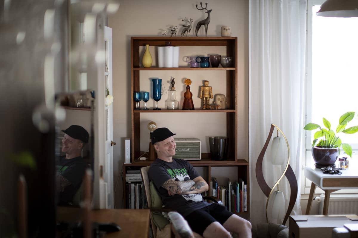 Iivari Viilosmaa kotonaan, joka on täynnä design-keräilytyotteita.