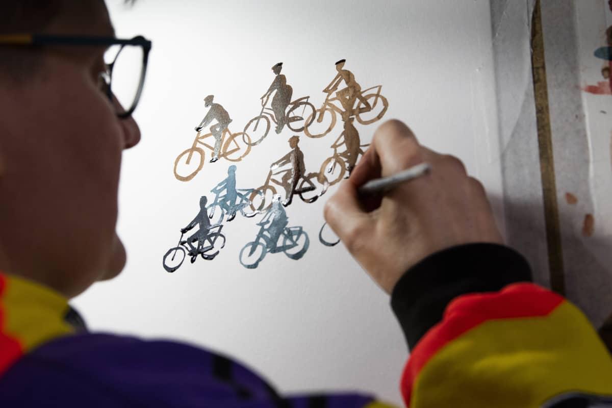 Sarjakuvataiteilija Tiitu Takalo maalaa kapealla siveltimellä pyöräilijöitä.