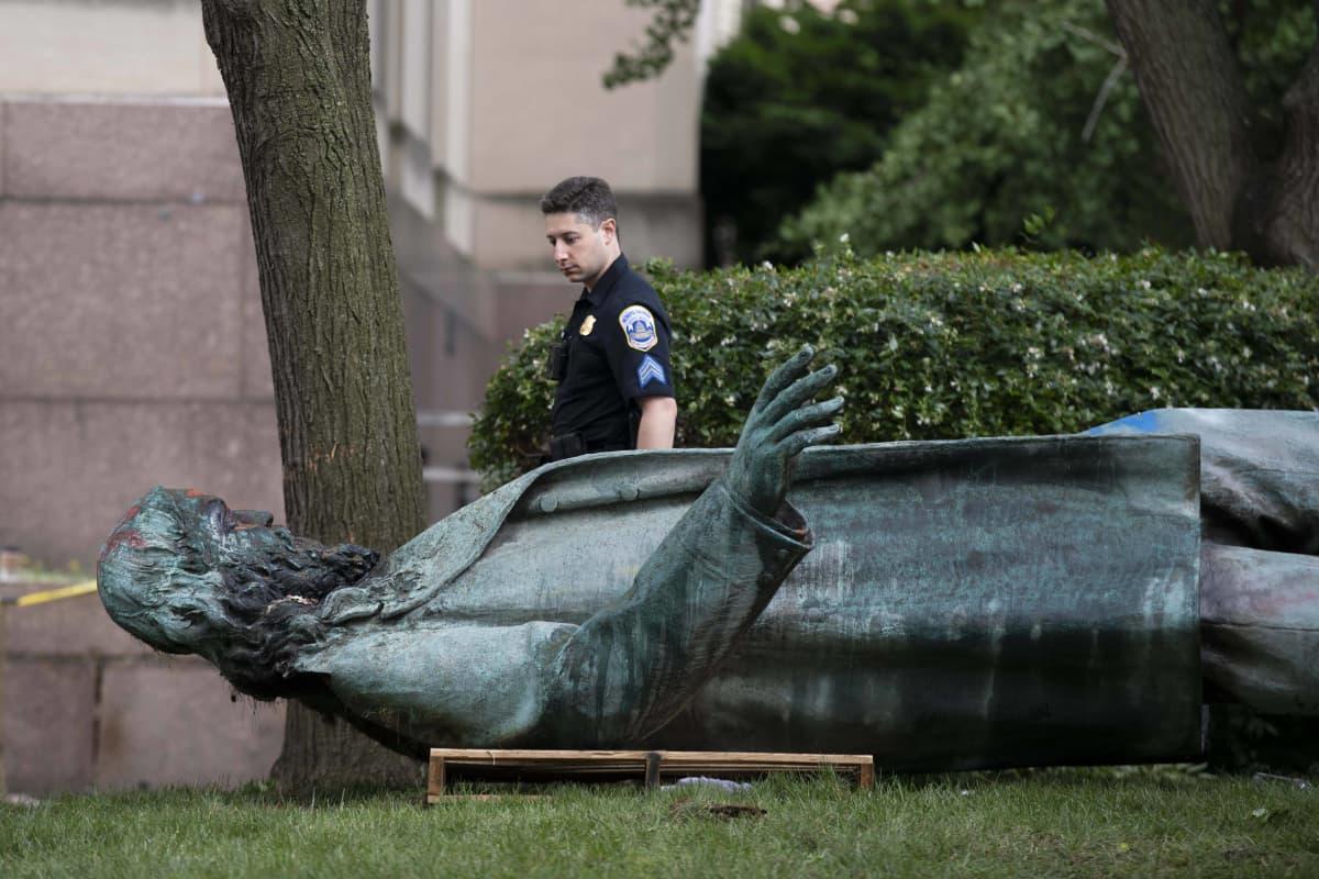 Poliisi katsoo maahan kaadettua patsasta.