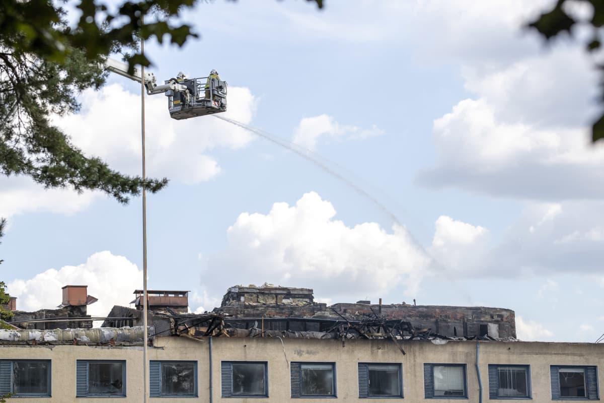 palomiehet suihkuttavat vettä nosturista palaneen talon ullakolle