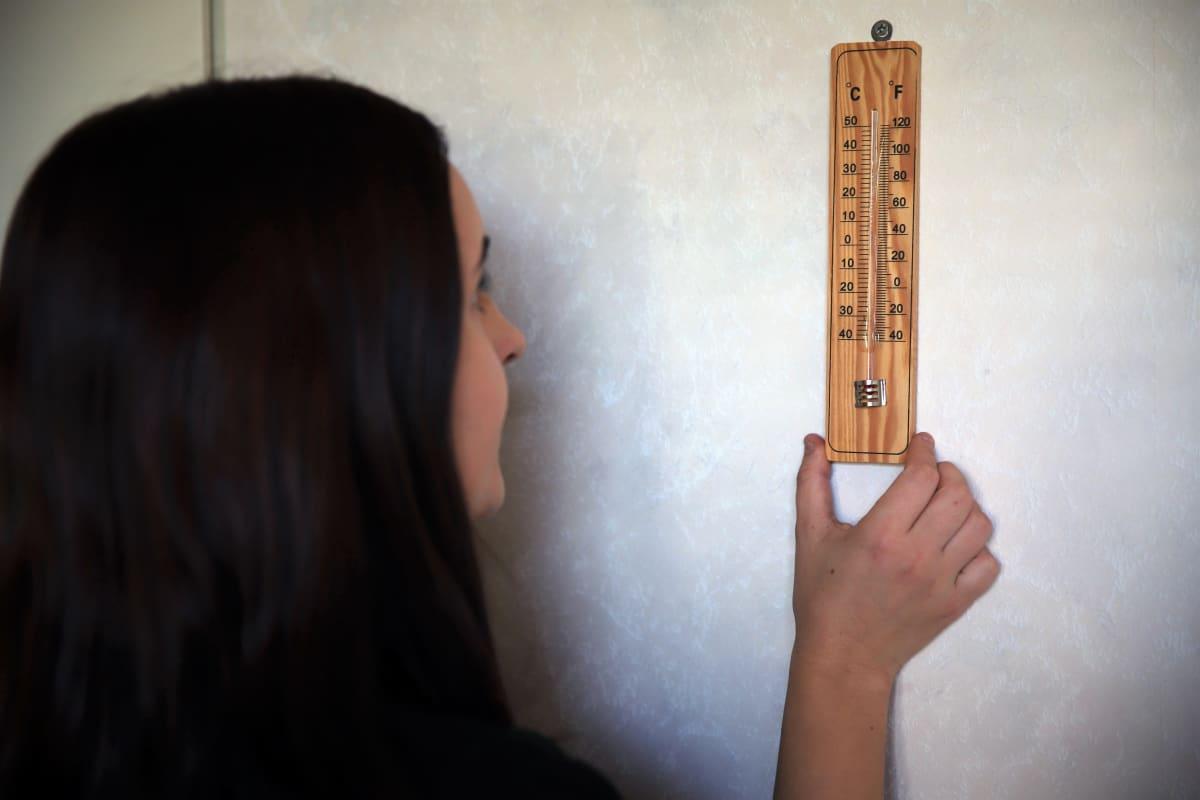 Mikkeliläinen Miia Laitinen katsoo kotinsa sisälämpötilaa lämpömittarista.