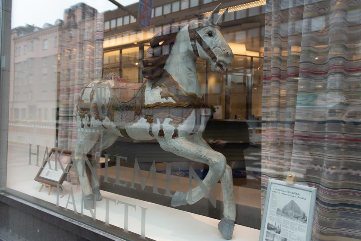 Puinen vanha hevonen näyteikkunassa.