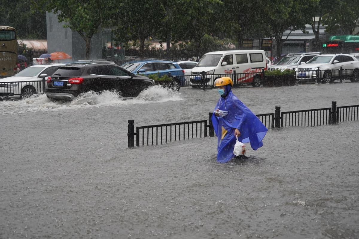 Sadeviittaan pukeutunut ihminen kahlaa tulvavedessä. Taustalla autoja vedessä.