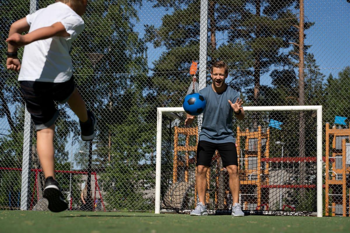 Poika potkaisee lasten sinistä kevyttä jalkapalloa etualalla, molemmat jalat ilmassa. Maalivahtina mies valmistautuu ottamaan ilmassa liitävän pallon kiinni.