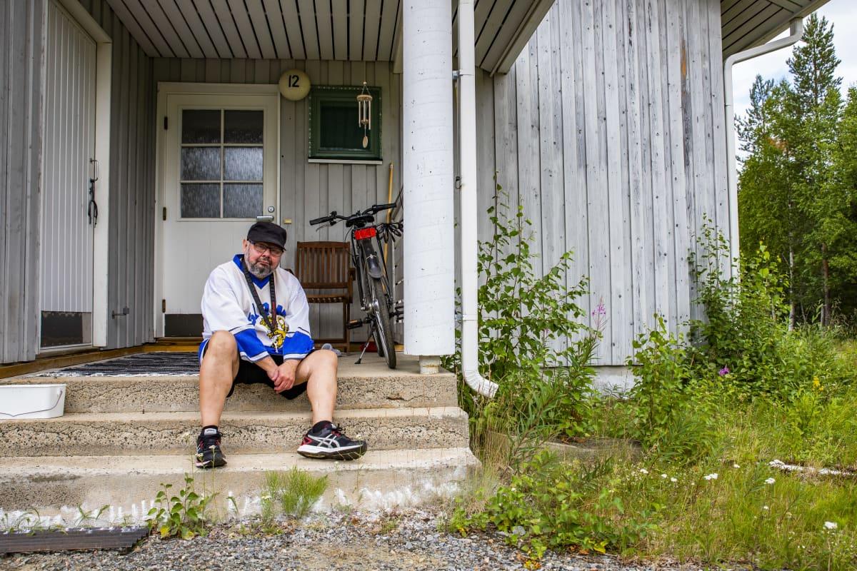 Ilkka Koskikara istuu oman asuntonsa portailla.