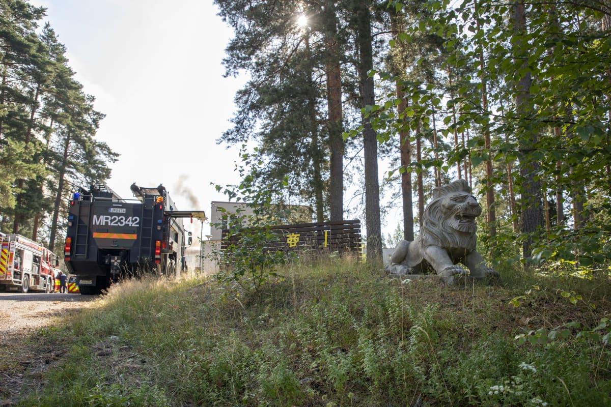 Leijonapatsas metsikön laidalla, taustalla puolustusvoimien pelastusyksikön auto