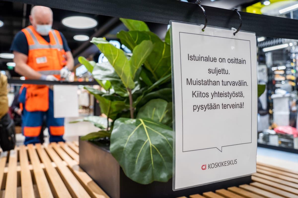 Työmiehiä asentamassa aitausta Koskikeskuksen yleisöpenkeille.