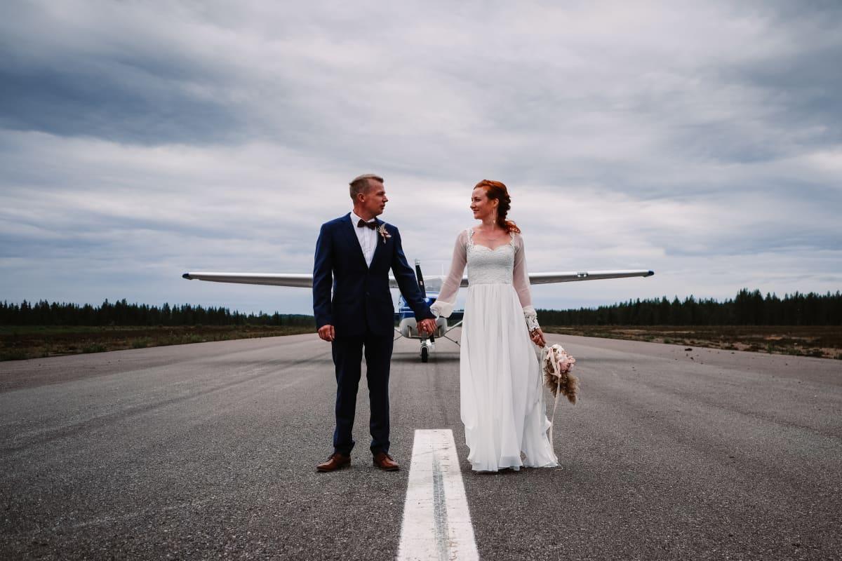 Hääpari seisoo lentokentän kiitotiellä toisiaan kädestä pidellen. Taustalla lentokone