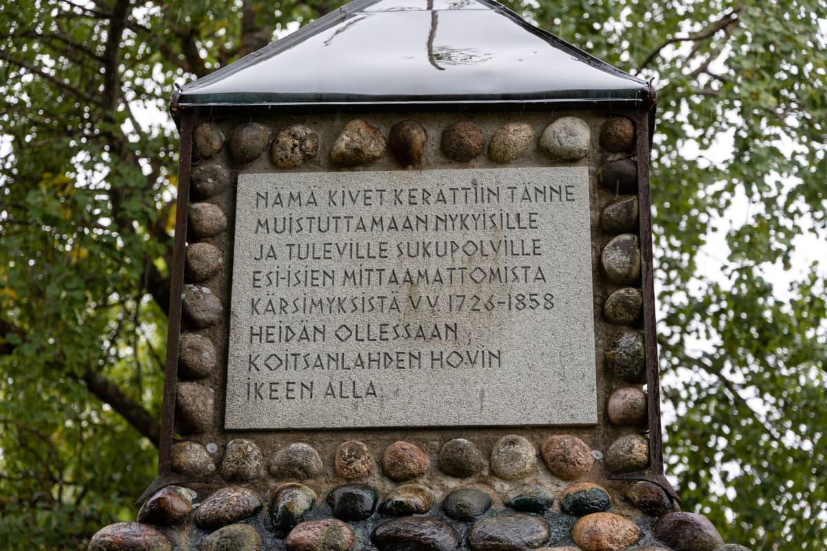 """Koitsanlahden hovin pihalla Parikkalassa muistomerkki: """" Nämä kivet kerättiin tänne muistuttamaan nykyisille ja tuleville sukupolville esi-isien mittaamattomista kärsimyksistä vuosina 1726-1858 heidän ollessaan Koitsanlahden hovin ikeen alla."""""""