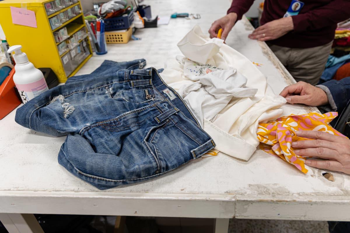 Kierrätykseen annettuja vaatteita pöydällä Imatran Saimaan Virta työpajassa.