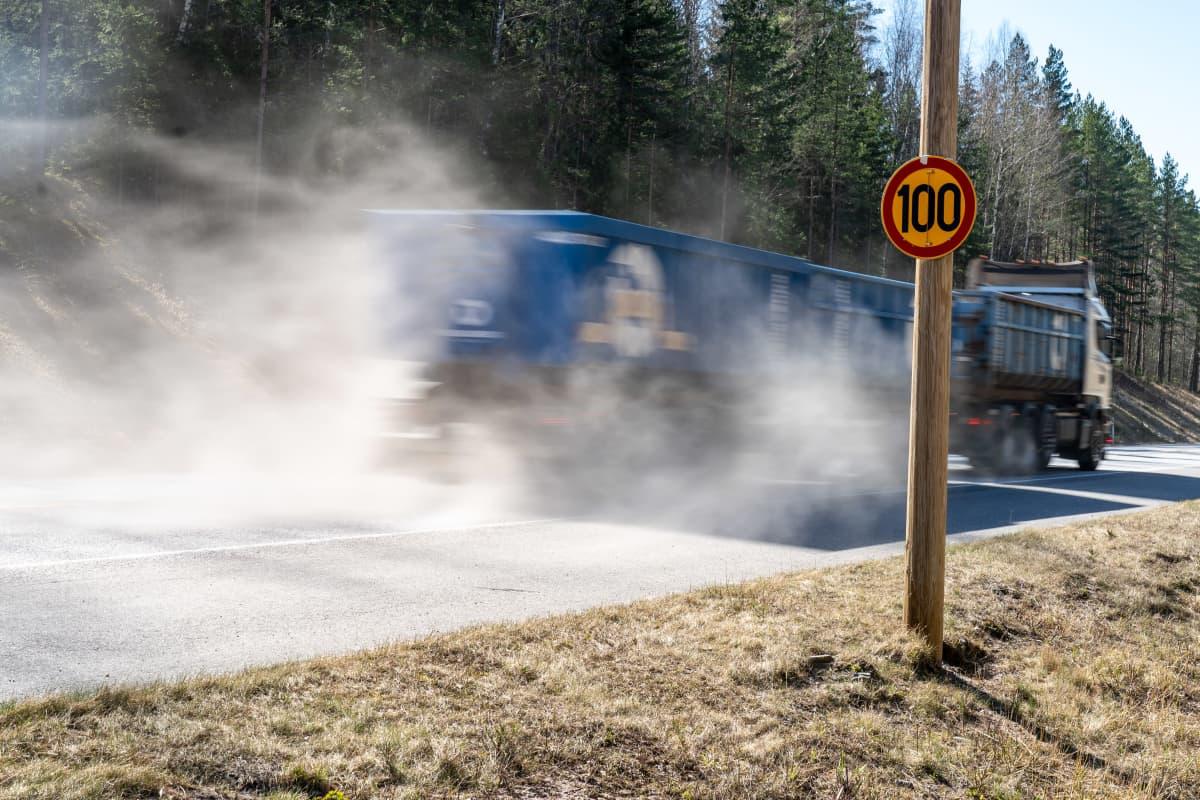 Täysperävaunuyhdistelmä nostattaa pölypilven maantiellä.