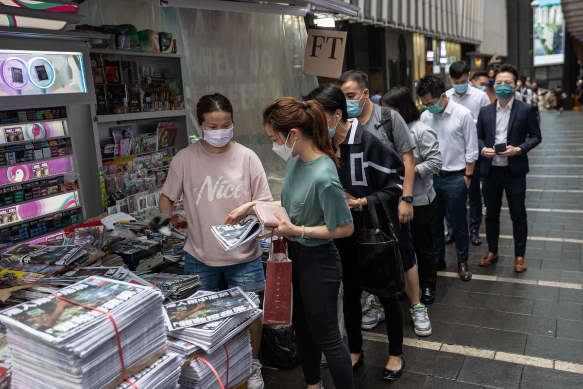 Ihmiset jonottivat Apple Dailyn viimeistä painosta varhain aamulla Hongkongissa.