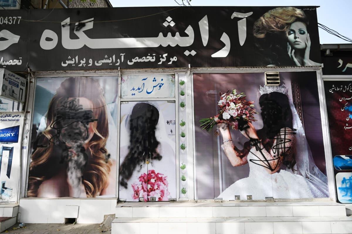 Reklam för en skönhetssalong i Kabul 18.8.2021. Översprayade kvinnoansikten.