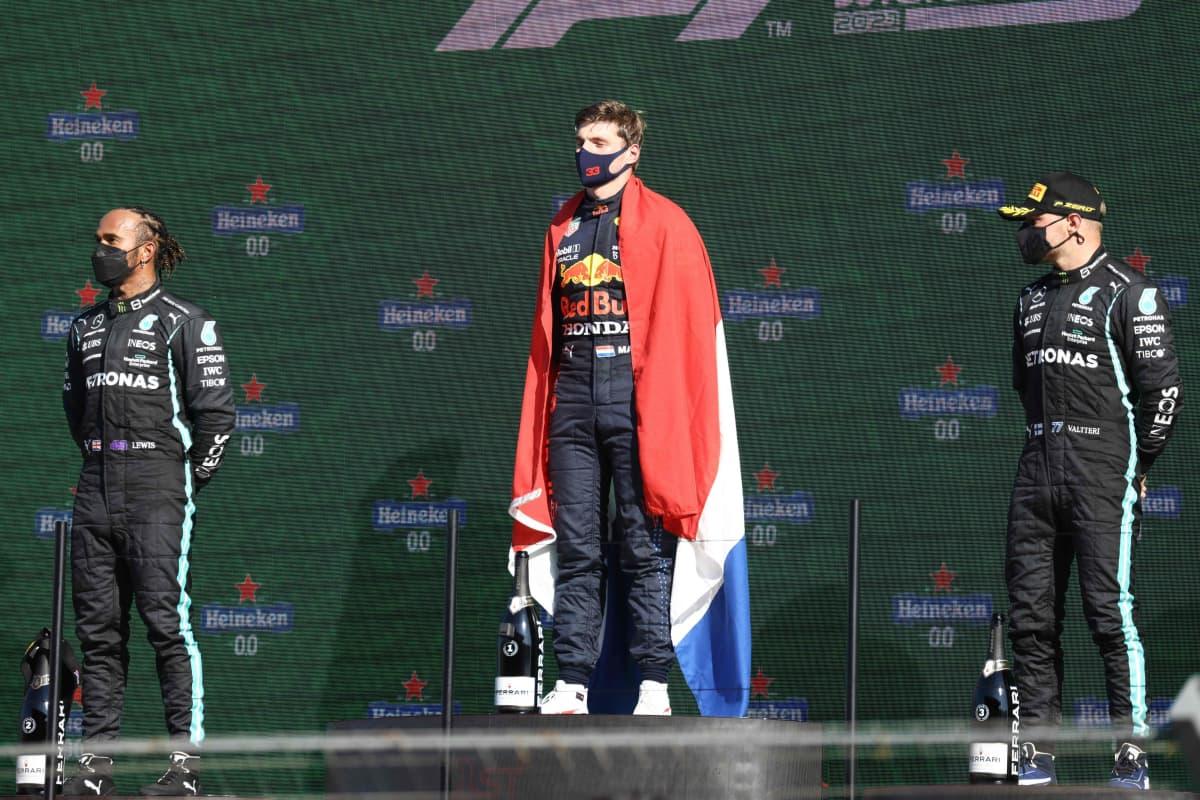 Max Verstappen palkintokorokkeella kietoutuneena Hollannin lippuun. Vierellä Lewis Hamilton (oik.) ja Valtteri Bottas.
