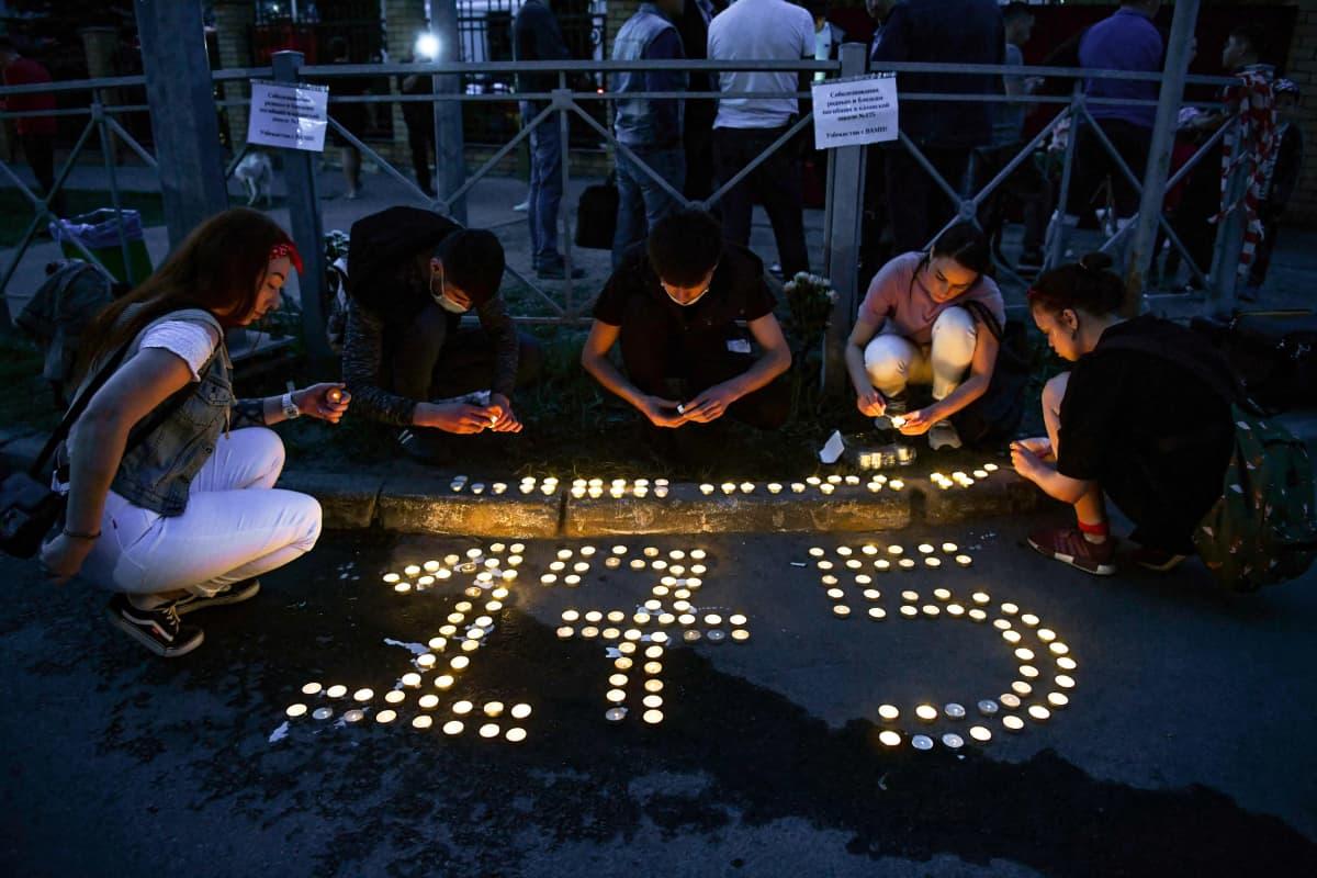 Nuoret sytyttävät kynttilöitä kouluammuskelupaikan edustalla.