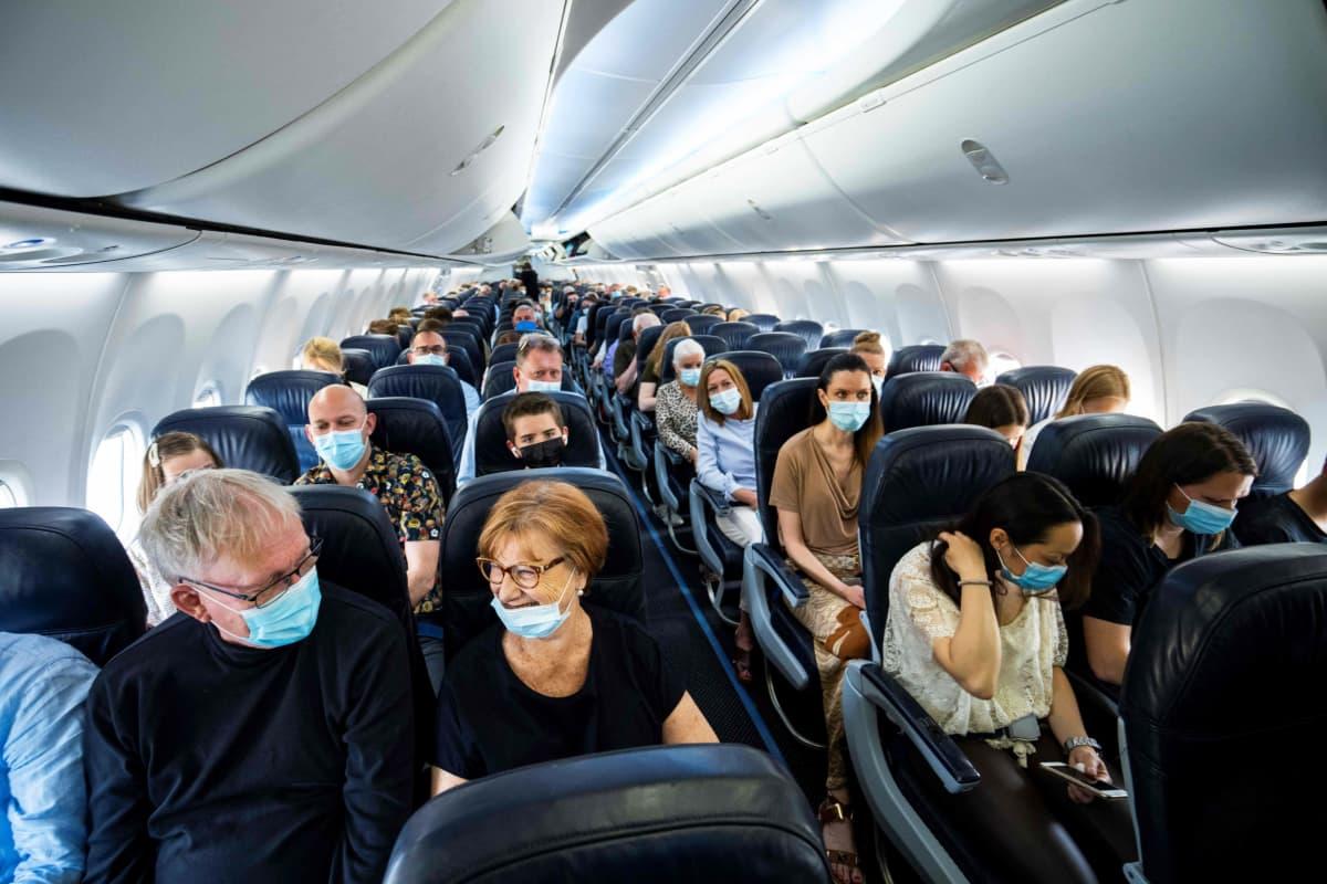 Lentokone täynnä kasvomaskeihin pukeutuneita matkustajia.