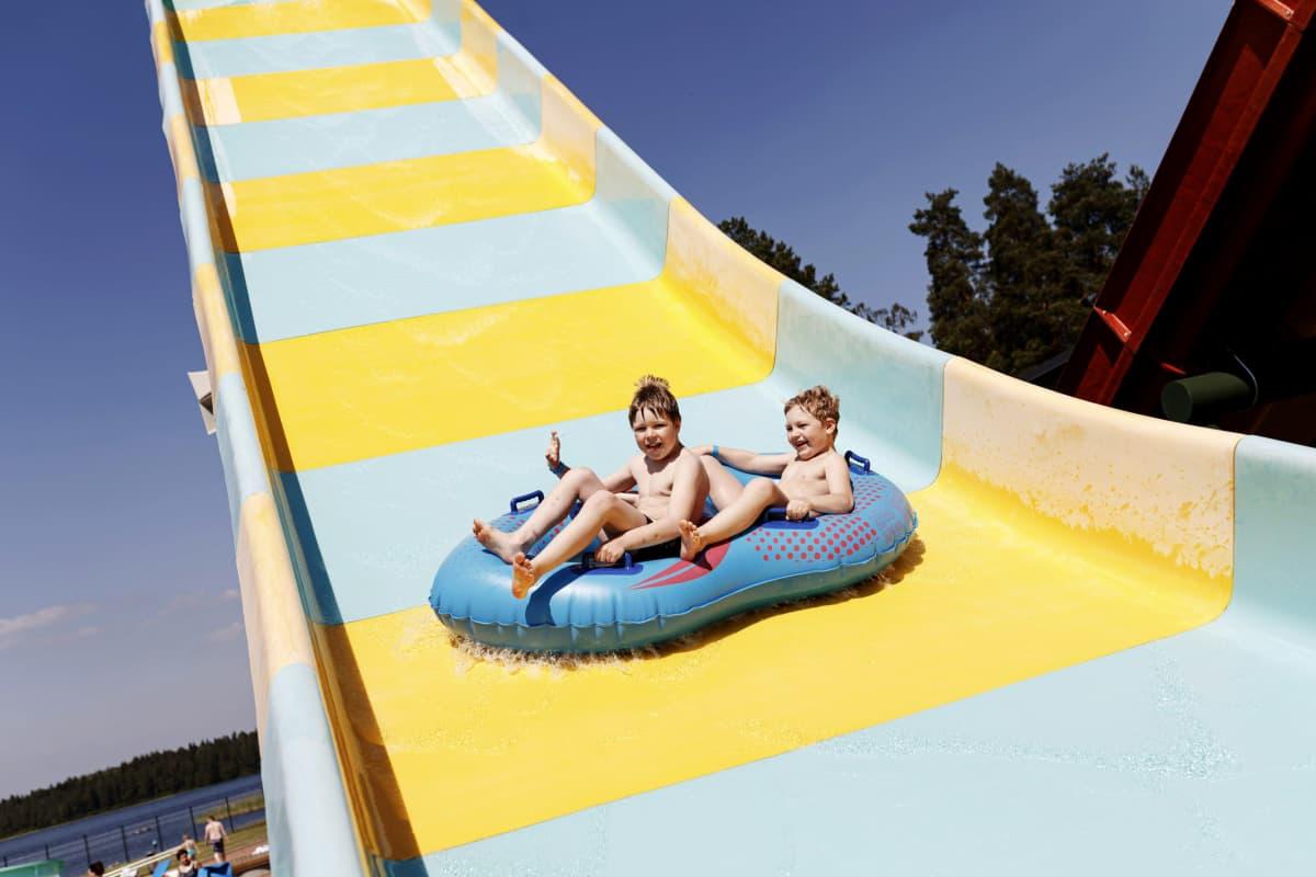 Lapset nauttivat vesileikeistä ja kesähelteestä vesipuistossa.