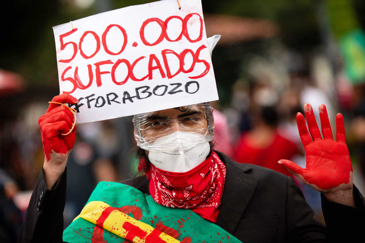 Mielenosoittaja punaisiksi maalattuine käsineen pitelee kylttiä.