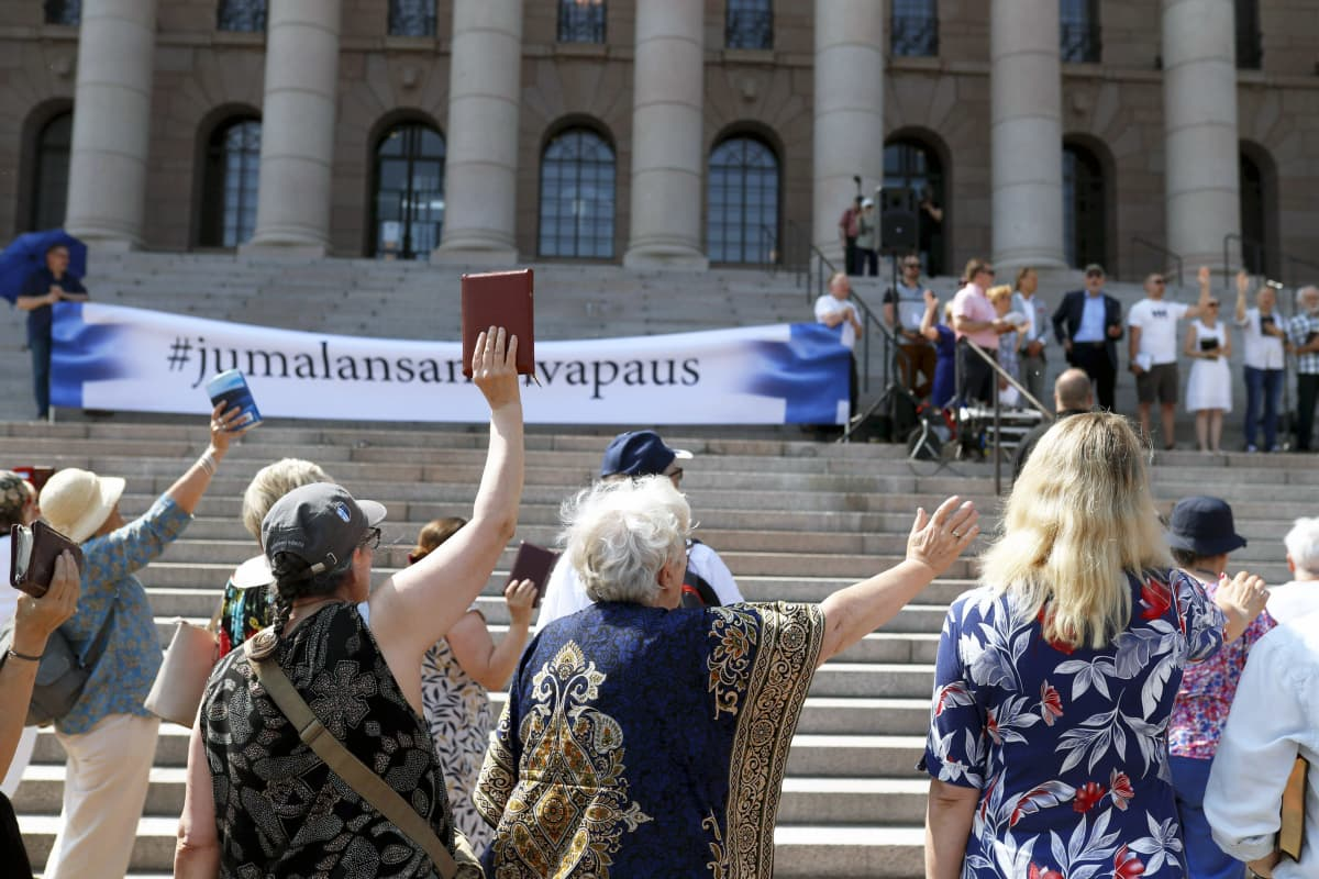 Mielenosoittajat heiluttelevat raamattuja eduskunnan edustalla.