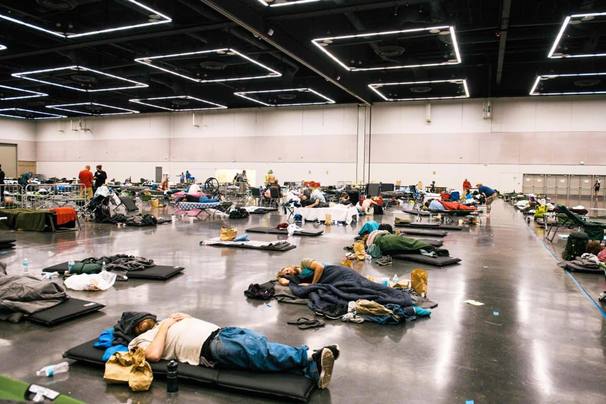 Ihmiset makaavat konferenssikeskuksen lattialla.