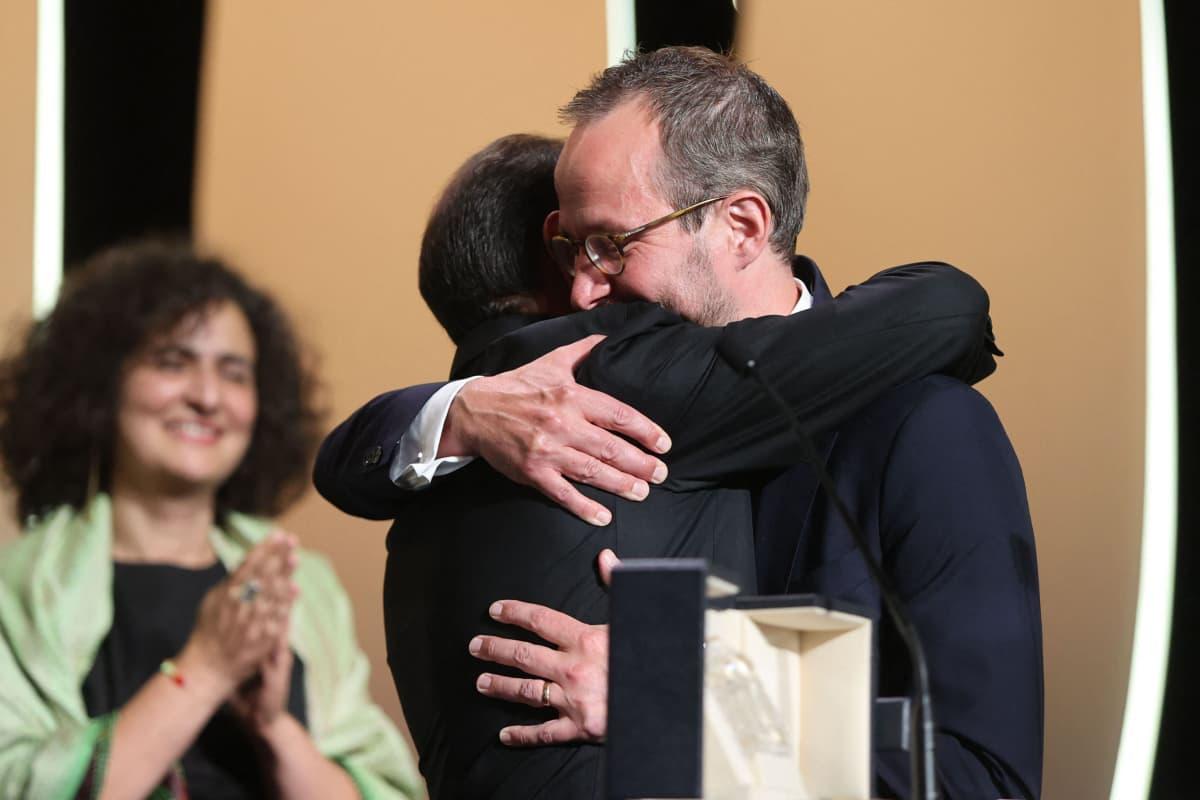 Suomalaisohjaaja Juho Kuosmanen ja iranilainen elokuvaohjaaja Asghar Farhadi onnittelevat toisiaan jaetun Grand Prix -palkinnon voitosta.