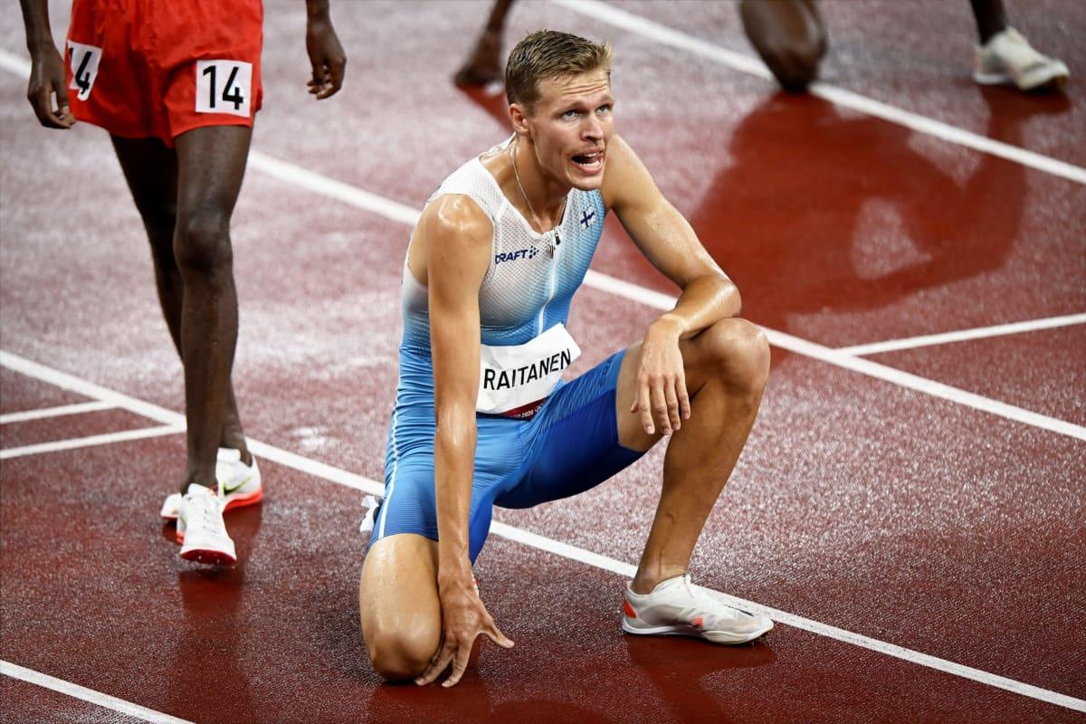 Topi Raitanen står i knästående efter målgång.