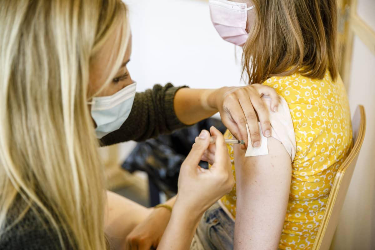 Nuori henkilö saa koronarokotteen Energia-areenan rokotuspisteessä.