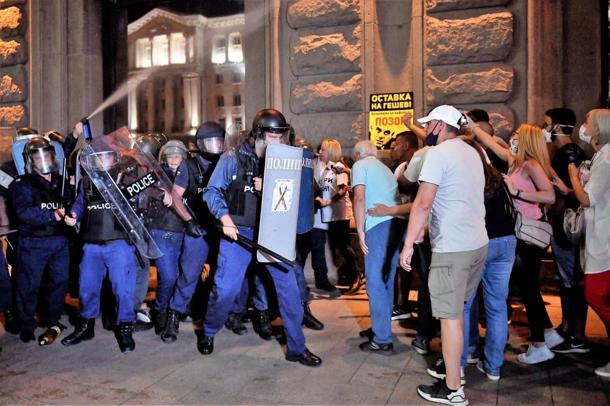 Mellakkapoliisit ja mielenosoittajat seisovat vastakkain. Mellakkapoliisit pitävät kilpiä edessään. Mielenosoittajat huutavat heille.