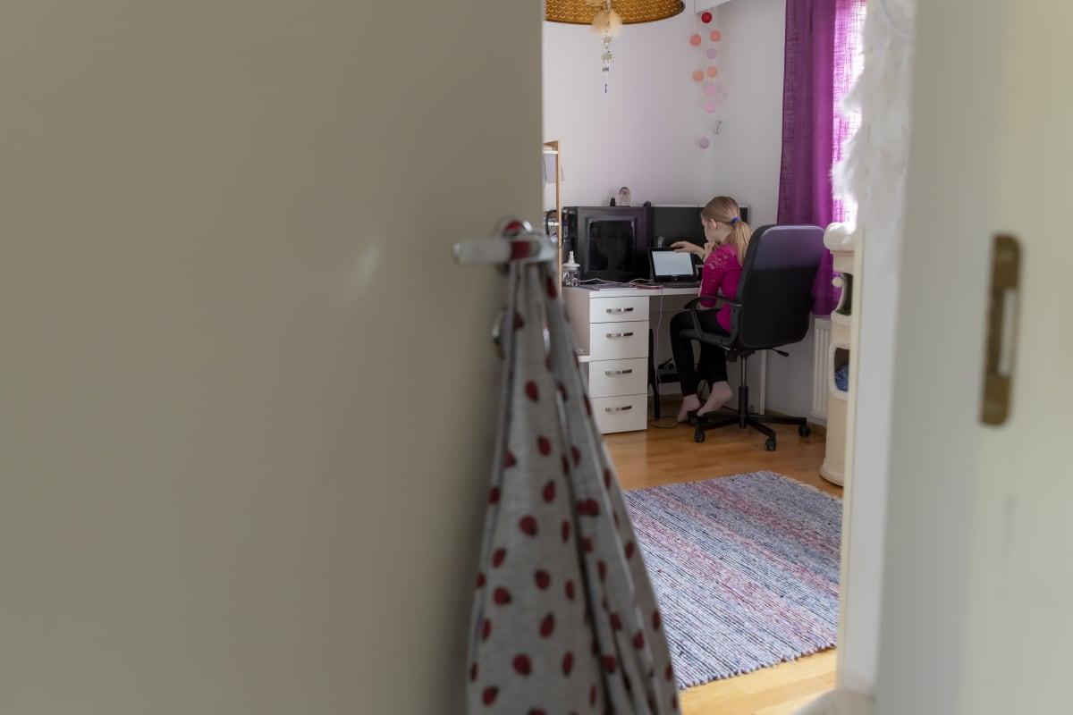 Koululainen istuu huoneessaan tietokoneella