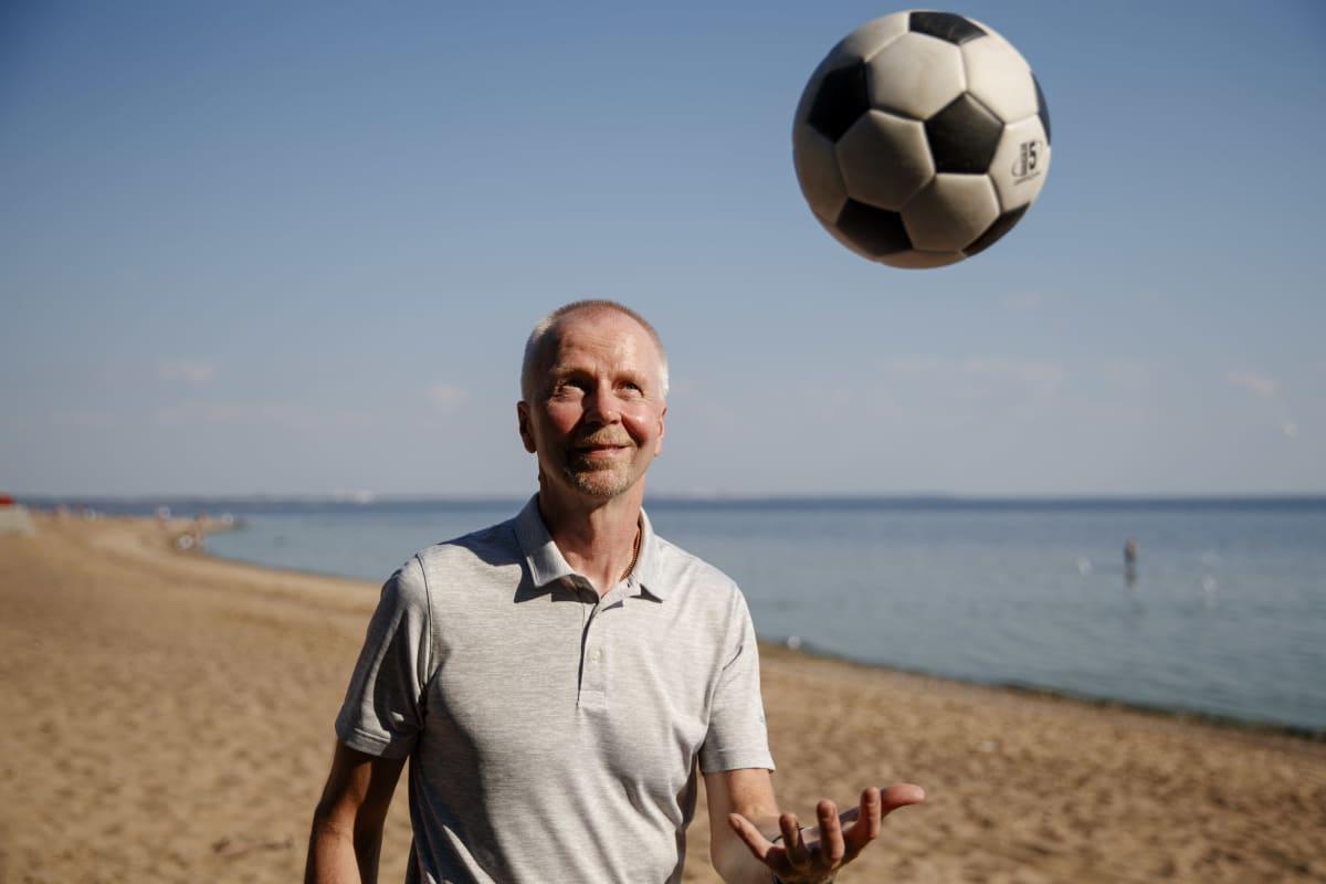 Yle Urheilun asiantuntija Olli Huttunen heittää palloa ilmaan rannalla Repinossa 20.6.2021.