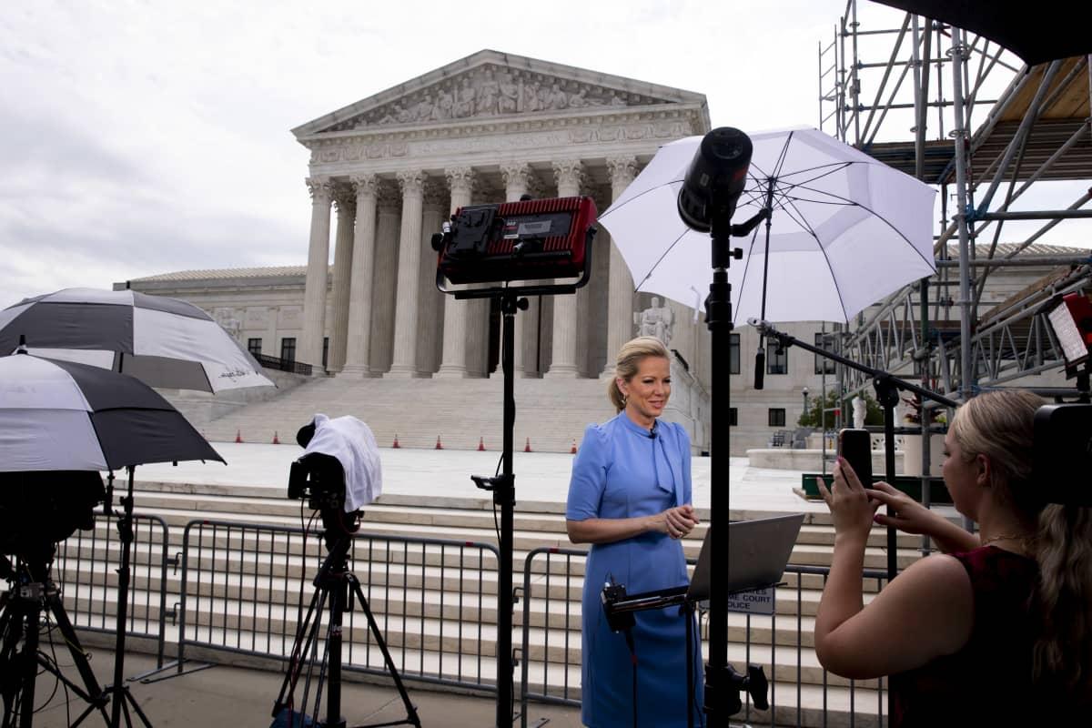 Uutistoimittaja nainen seisoo kameran edessä, taustalla Yhdysvaltain korkeimman oikeuden rakennus.